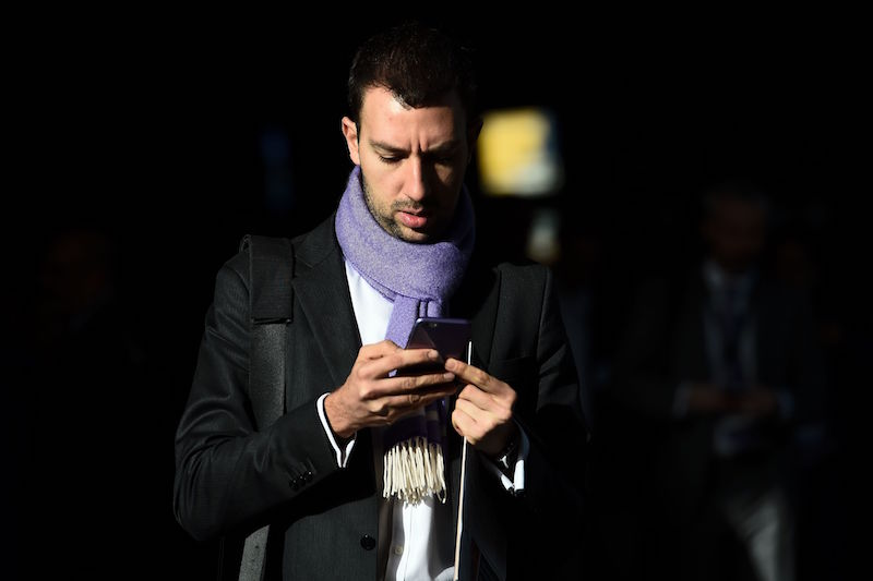 man in coat and scarf looking at his phone