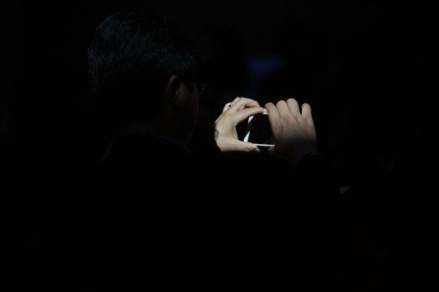 hands on a smartphone in darkness