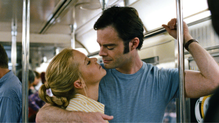 Bill Hader is holding onto a pole on the subway train and is about kiss Amy Schumer.