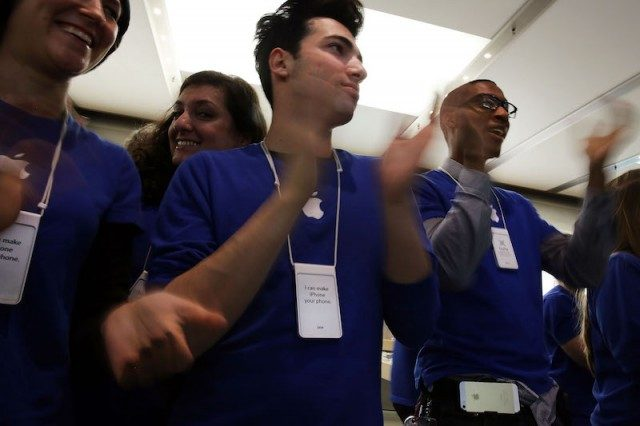 Apple Store employees cheer as the first customers in line walk into the store