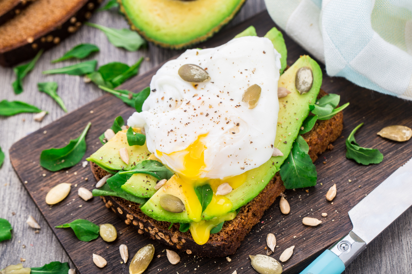 breakfast sandwich with a poached egg, sliced avocado, and greens on whole-grain bread