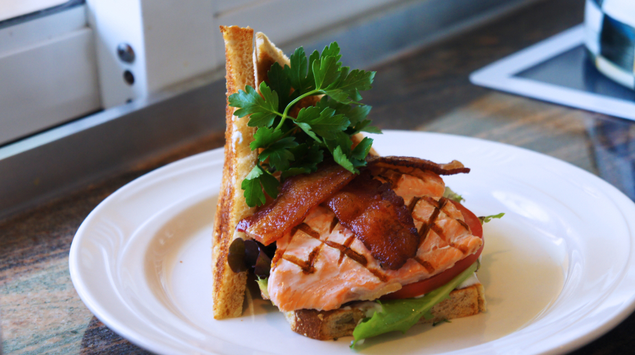 hearty grilled salmon sandwich with lettuce, tomato, and bacon