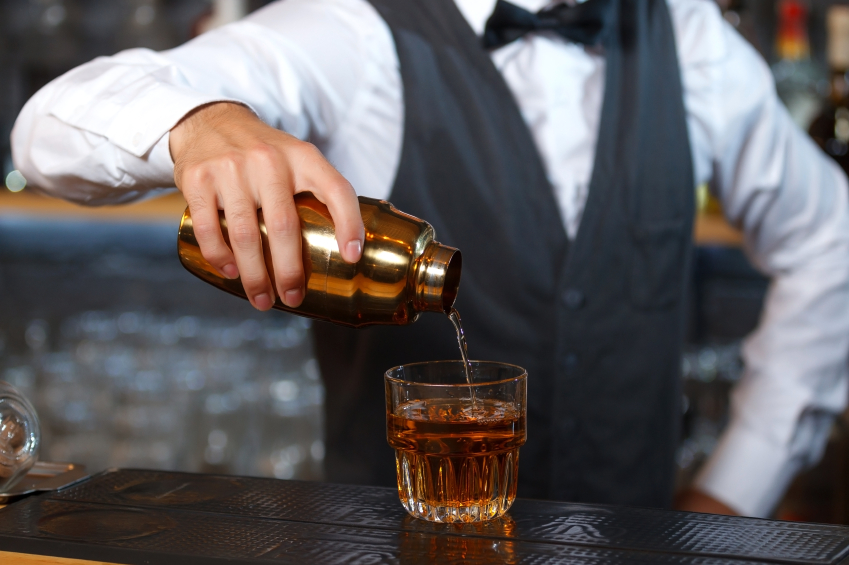 bartender holding a golden shaker in his hand and pouring a cocktail