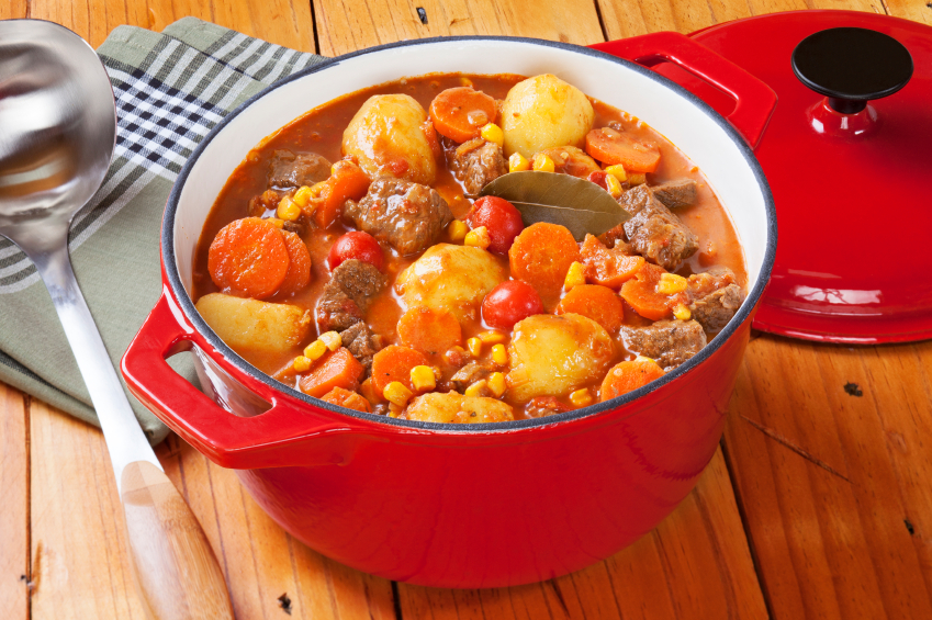 beef stew with carrots, potatoes, an corn in a red pot