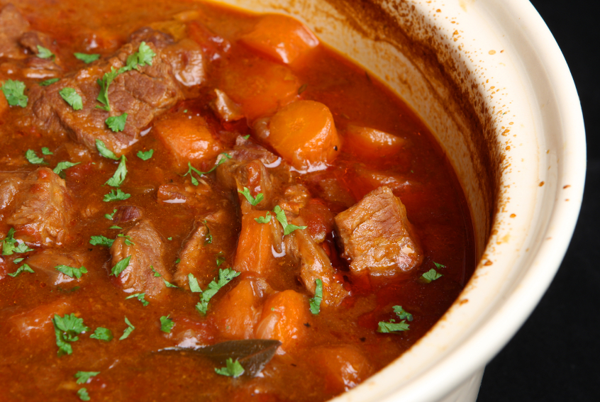 beef stew in a ceramic dish with tomatoes and carrots