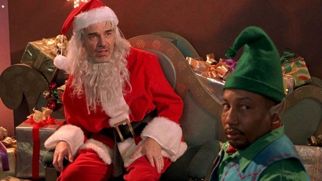 Billy Bob Thornton sitting in a chair in front of an elf in 'Bad Santa.'