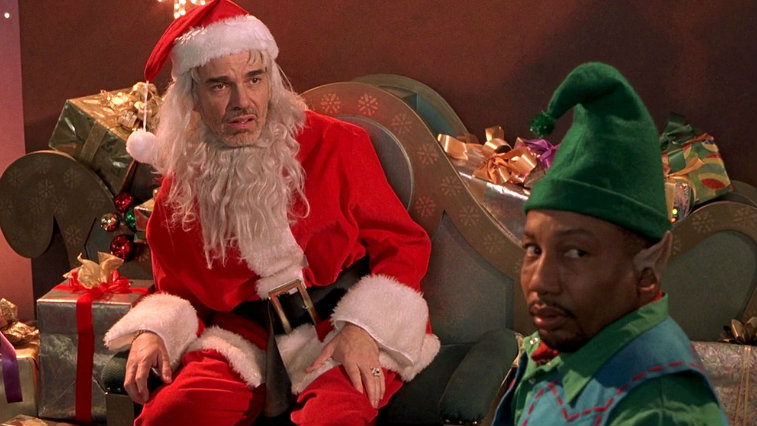 Billy Bob Thornton sits in a chair as Santa while a man dressed an elf stands next to him in front of a pile of gifts