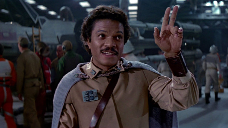 Lando waves with two fingers and smiles