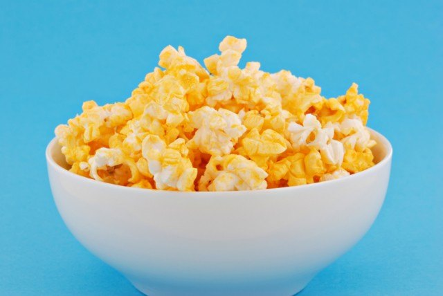 White bowl filled with buttered popcorn.