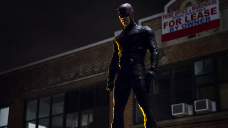 Daredevil in his full suit, standing on a rooftop and looking down