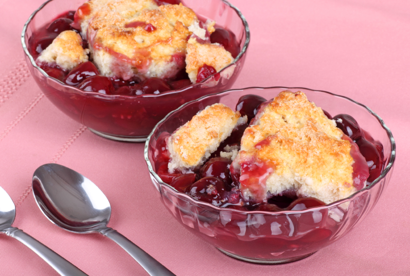 two bowls filled with cherry cobbler that has a biscuit topping