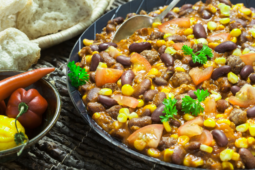 cast-iron skillet filled with chili that has tomatoes, corn, and beans