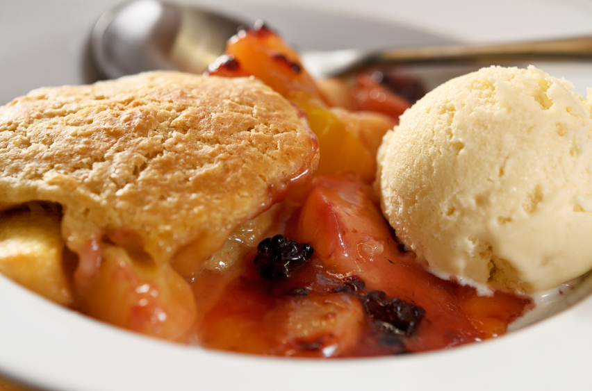 bowl filled with juicy fruit cobbler and a scoop of ice cream
