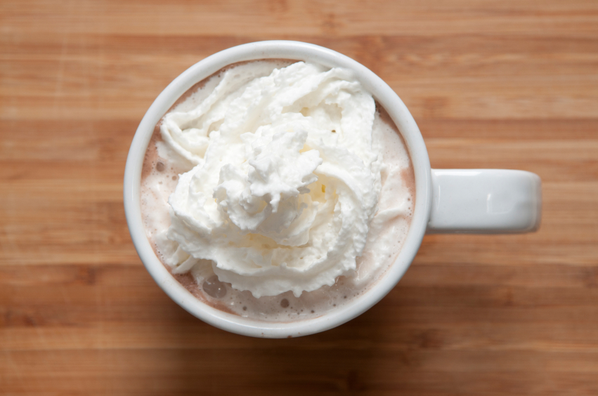 overhead view of a mug of hot chocolate with whipped cream