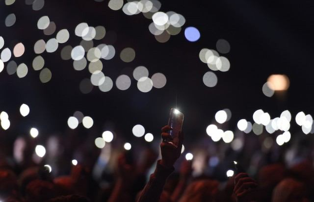 person holding up their phone with concert lights all around them