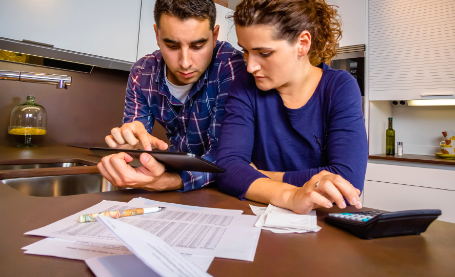 man and woman looking at a tablet with bank account statemnts and calculator on a table