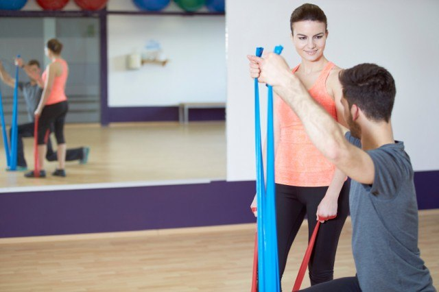 Man and woman practice resistance band training