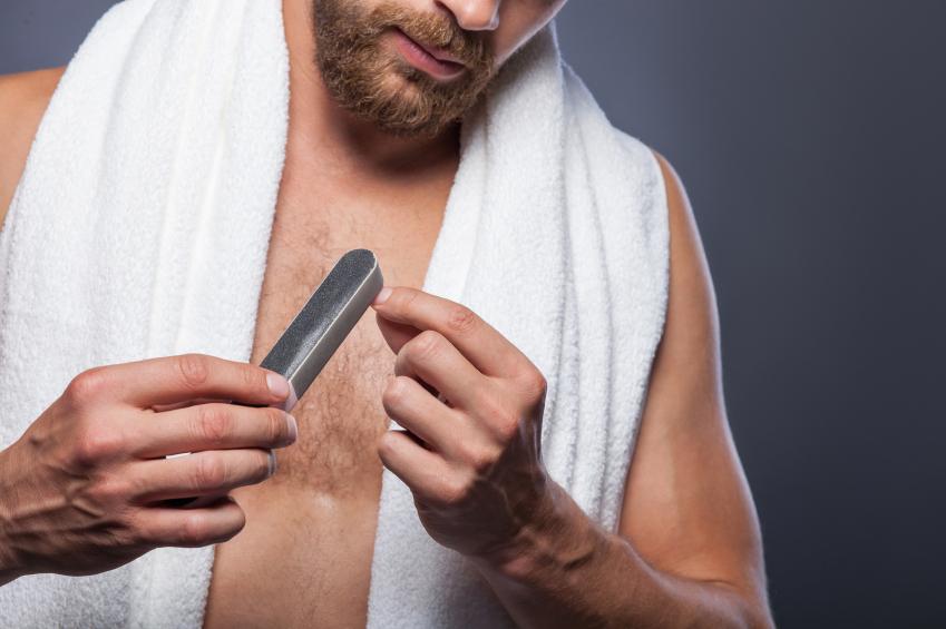 bearded guy is making manicure