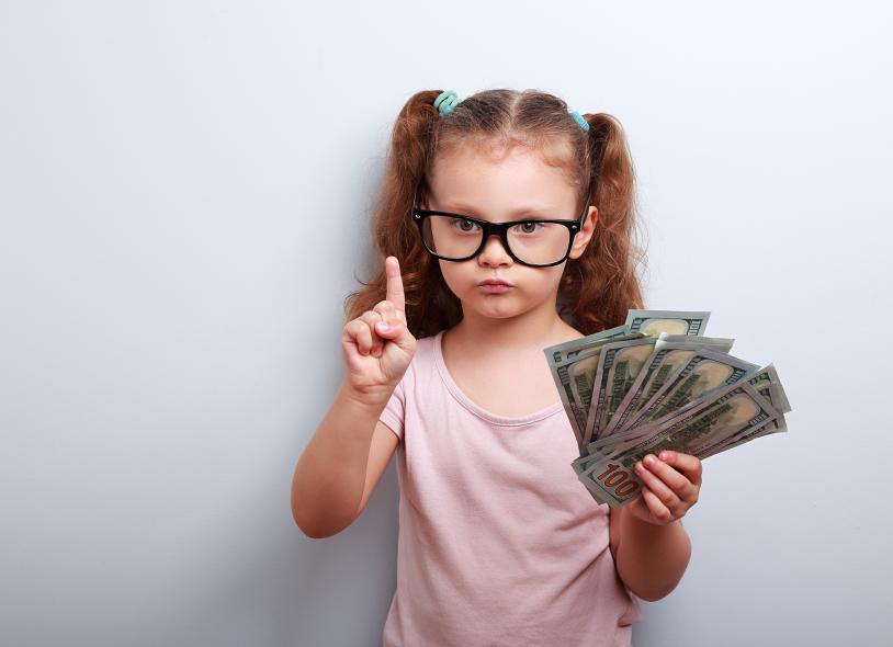 Cute kid girl wearing eyeglasses holding dollars