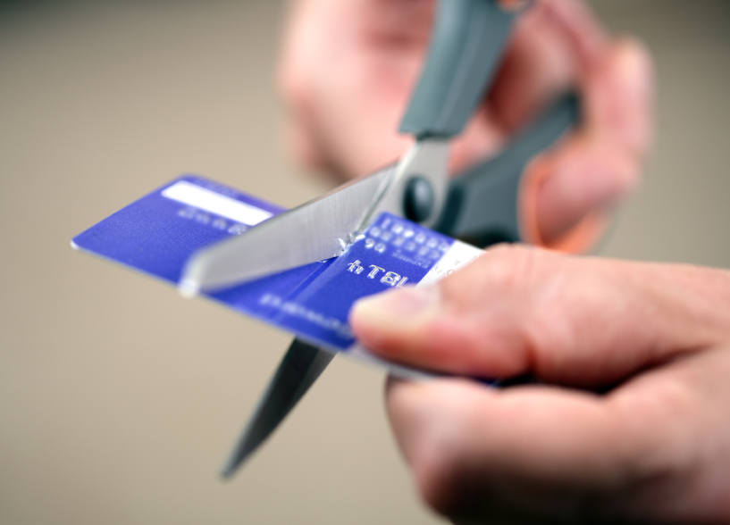 man cutting a credit card with scissors