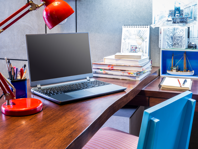 a laptop on a desk and with pen holder and table lamp