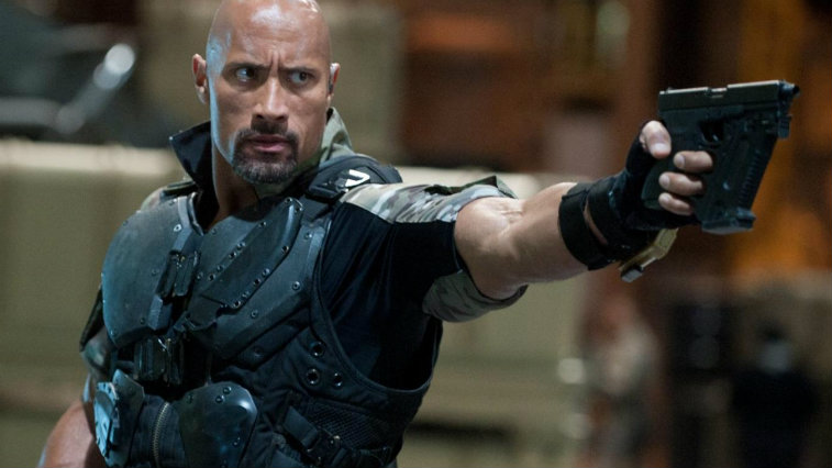 Dwayne Johnson is wearing body armor and is pointing a gun in Fast Five.