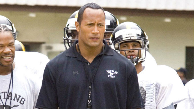 Dwayne Johnson is on the sidelines and is dressed as a football coach in Gridiron Gang.