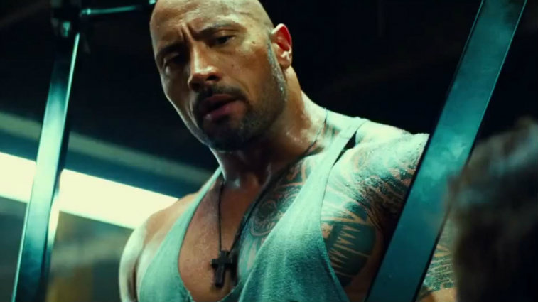Dwayne Johnson looks down at someone and is wearing a grey muscle shirt in Pain and Gain.
