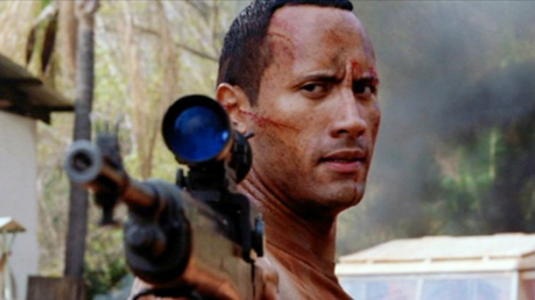 This is a closeup of Dwayne Johnson bloody and holding a gun in The Rundown.