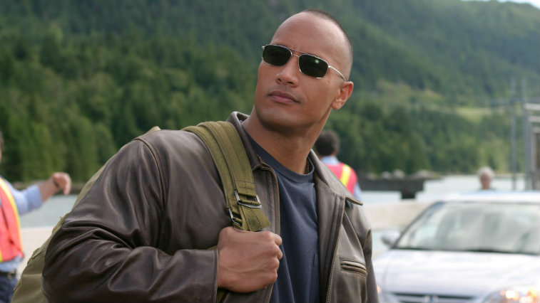 Dwayne Johnson is wearing sunglasses and has on a backpack in Walking Tall.