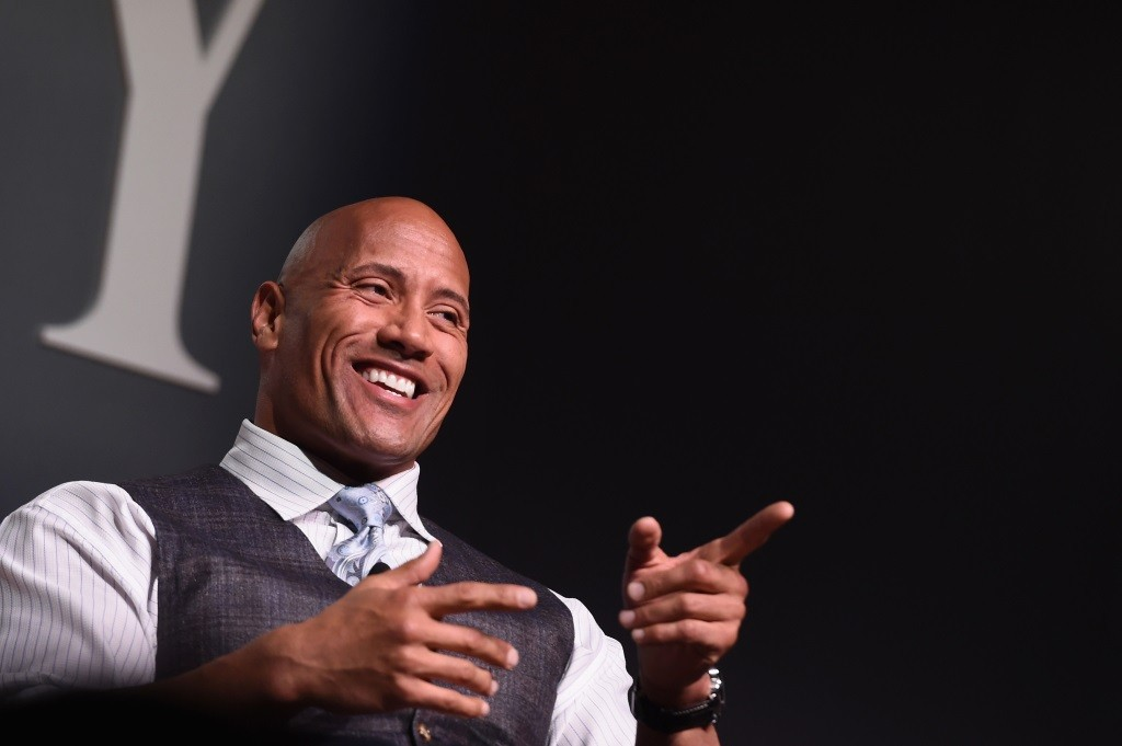 Dwayne 'The Rock' Johnson is smiling and pointing into a crowd.