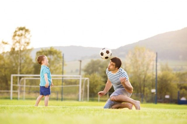 dad and son playing soccer