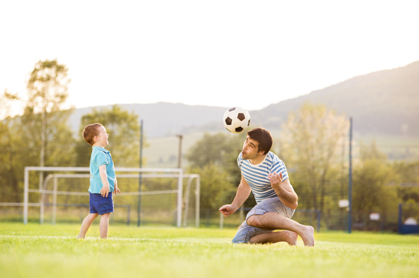 father and young son playing soccer at the park