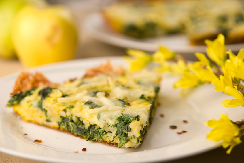 white plate with a slice of spinach and spaghetti frittata