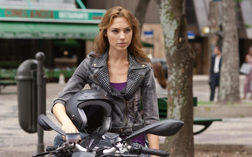 Gal Gadot as Gisele standing next to a motorcycle and holding a helmet in Fast & Furious