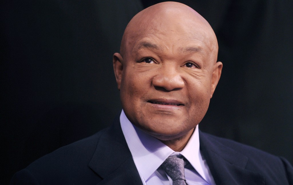 George Foreman is in a purple shirt and tie and dark jacket.