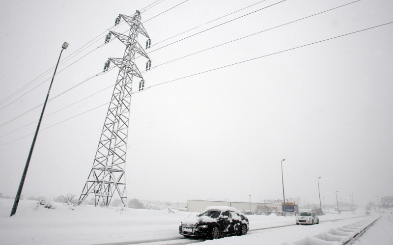 Cars drive past an electric pylon covere