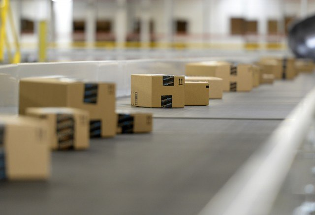 Amazon boxes make their way down the line in a warehouse from orders placed by Amazon Echo