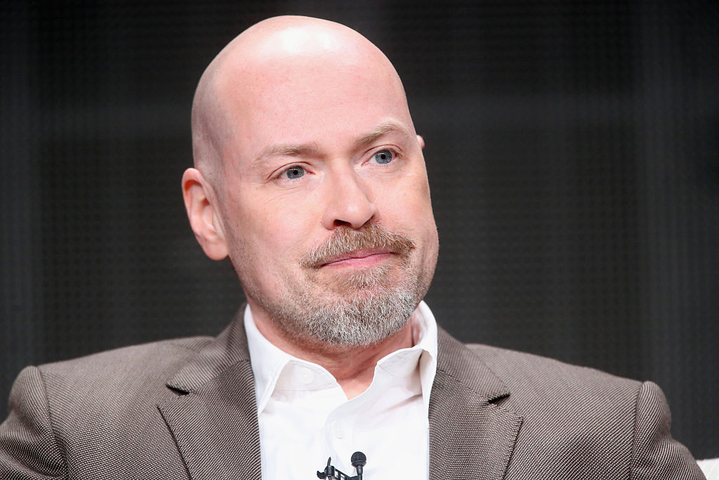 Steven DeKnight in a suit answering questions