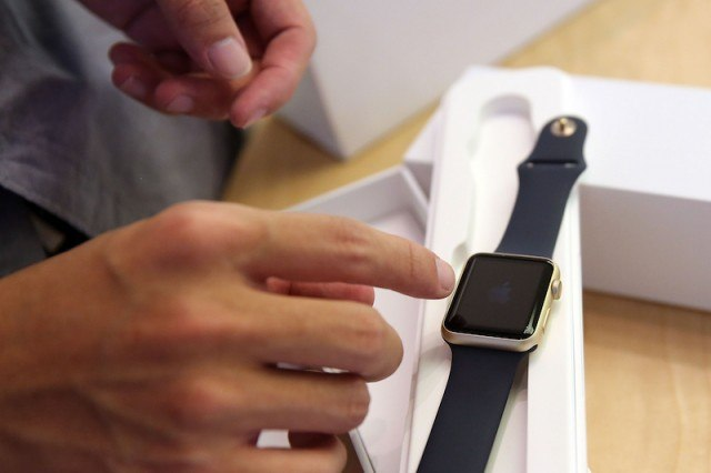 A person taking an Apple Watch out of its box.