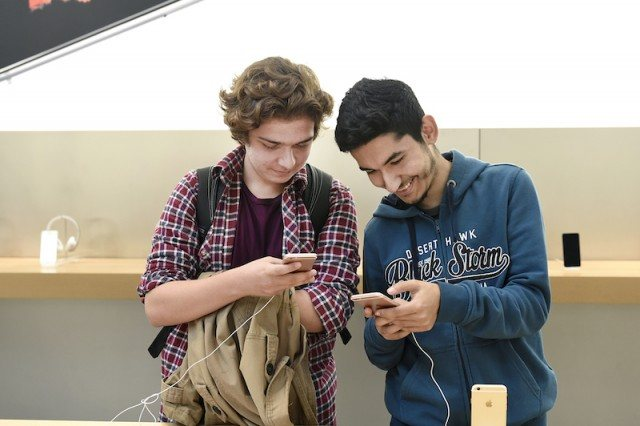 two men on their iPhones