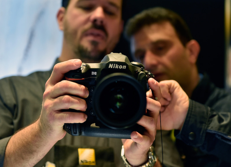 Two men look into a camera's display