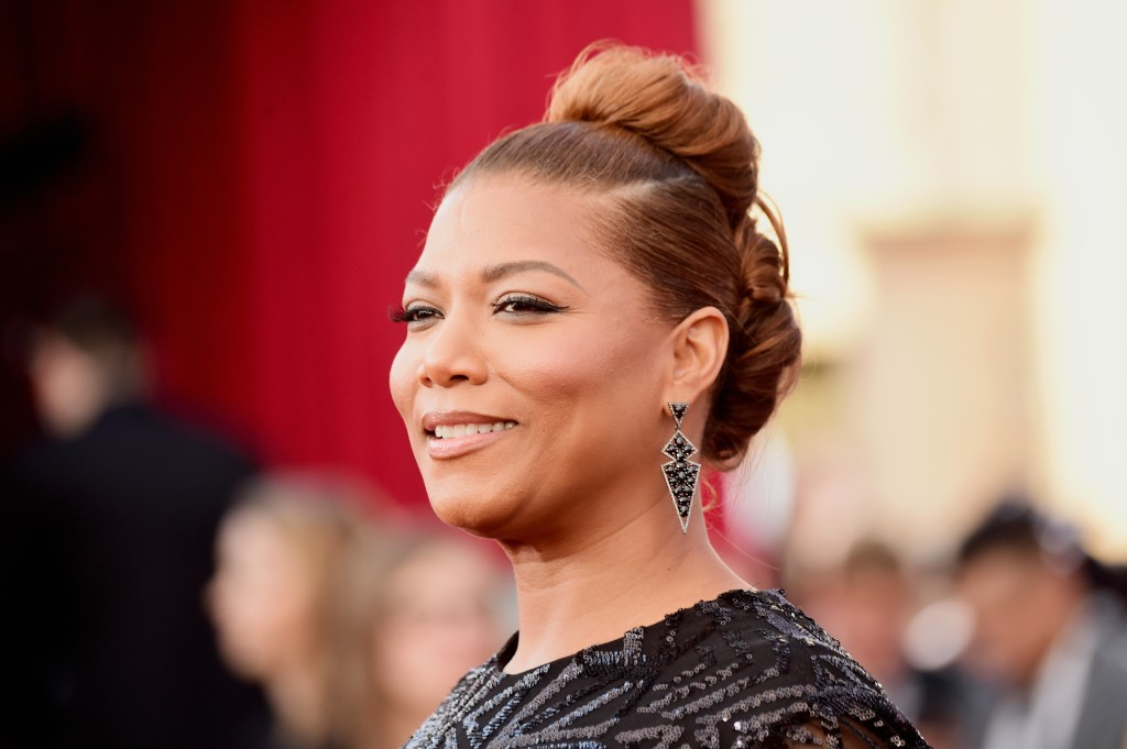 Queen Latifah is smiling on the red carpet.