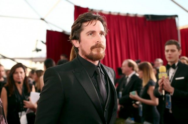 Christian Bale in a dark suit at a black-tie event.