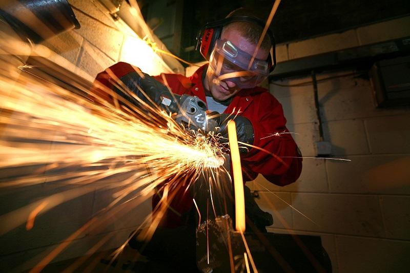 A man apprenticing in a machine shop