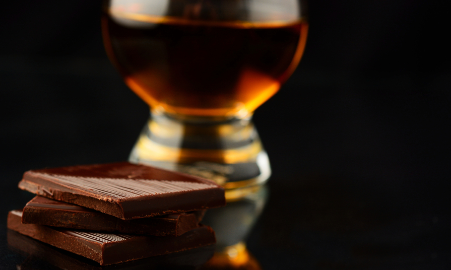 stack of dark chocolate with a glass of whiskey in the background