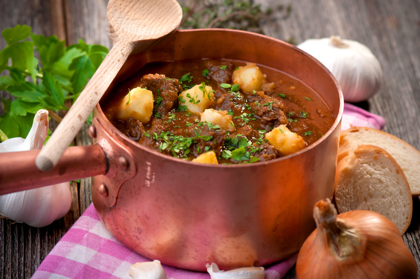 goulash stew in a copper pot sprinkled with parsley