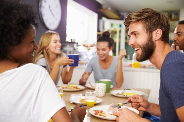 A group of friends shares a meal in a smart home with Amazon Echo