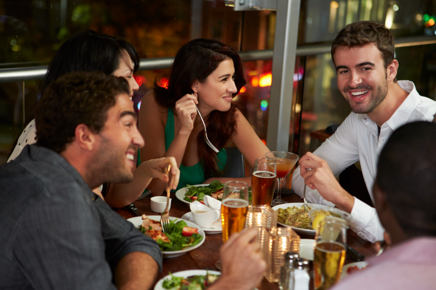A group of friends eat dinner at a restaurant.