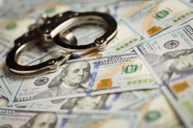 handcuffs on pile of money